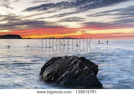 Colourful sunset at Currumbin Rock Gold Coast, with large rock and surfers