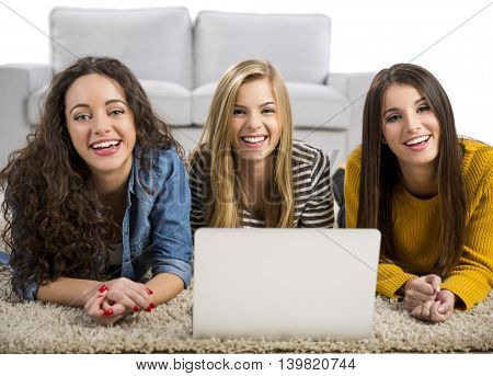 Happy teen girls studying at home with a laptop