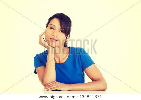 Pretty, happy, young woman in casual clothes sitting at the desk