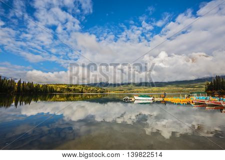 Cumulus clouds over the Pyramid mountain and Pyramid Lake. Wooden boat dock with moored pleasure boats