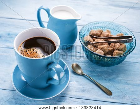 Cup of coffee, milk jug and cane sugar cubes on old blu wooden table.