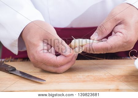Chef peeling shrimp before cooking / Cooking Pad Thai concept