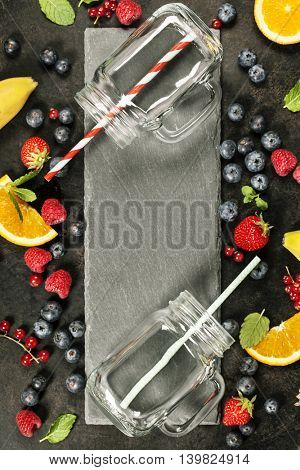 Smoothie ingredients and jars on dark rustic background