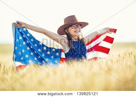 Pretty young pre-teen girl with an American cowboy hat in corn field and the holding American flag.