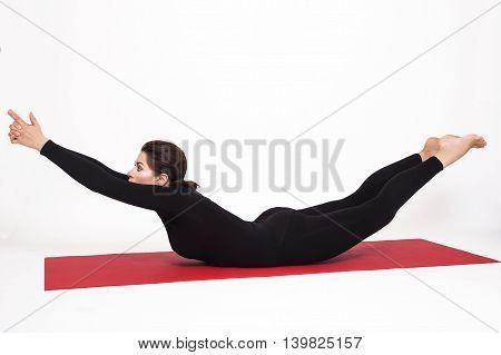 Beautiful athletic girl in black suit doing yoga. viparita naukasana asana boat pose. Isolated on white background.