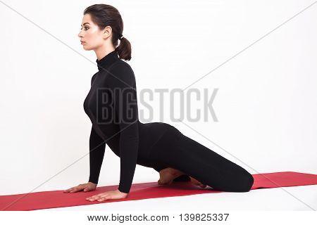 Beautiful athletic girl in black suit doing yoga. simhasana asana lion pose. Isolated on white background.