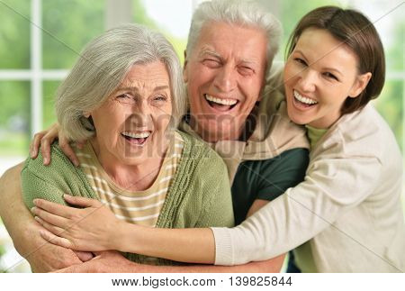 Happy senior parents with daughter on background