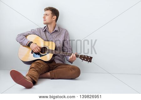 Portrait Of Handsome Man Playing Guitar Siting On Floor