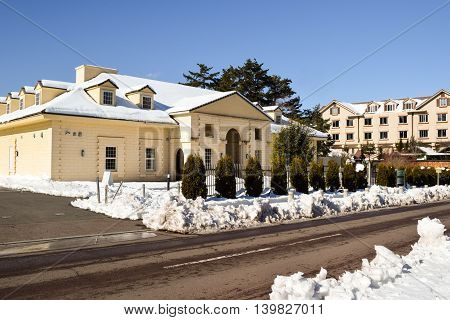 Large two storey brick building with snow covered roof and front yard.  Young trees border the fence to later become a hedge.  The road has been cleared of snow.