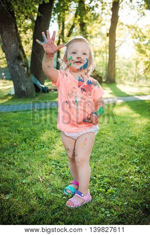 Two-year old girls stained in colors against green lawn