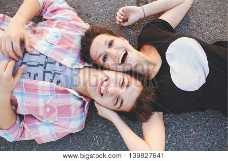 Teenage couple lying down and laughing. Loving girl and young man lying head to head. Top view.