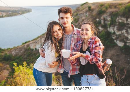 Friends drinking tea outdoors on landscape background. Hipster teenage friends hugging and holding a mug of coffee. Mug design concept.