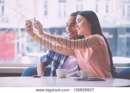 Smile. Happy and smiling young couple making selfie photo using smart phone while being in a cafe during their date