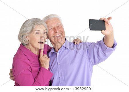 Portrait of a happy senior couple  taking selfie photo at white background