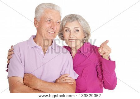 Portrait of a happy senior couple , woman pointing at white background