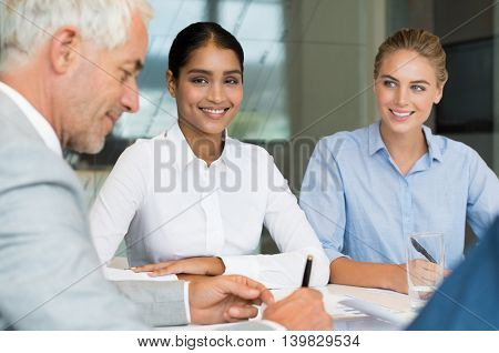 Portrait of multiethnic business woman sitting in a meeting room and looking at camera. Businesspeople discussing and working together during a meeting in a board room.