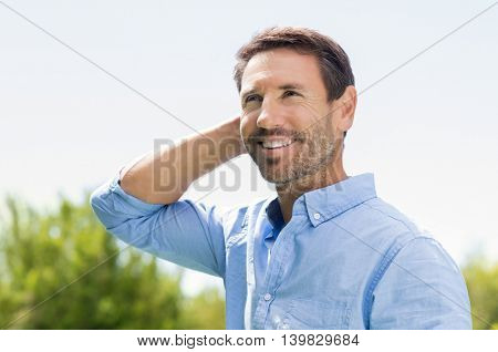 Portrait of smiling mature man looking up and thinking about his future. Cheerful man with beard standing with hand on head outdoor.