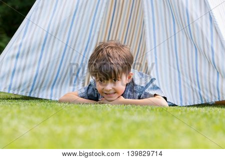Young boy enjoying camping trip. Cute little boy lying on front outside tent and looking at camera. Happy smiling child playing with indian tent in the garden.