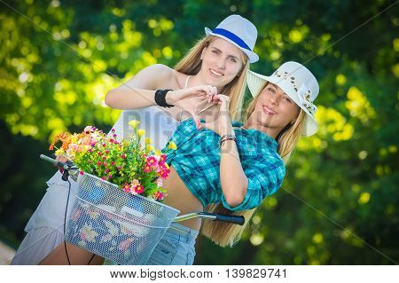 Two young females on bike making heart shape with their hands. Beauty, nature and love concepts.