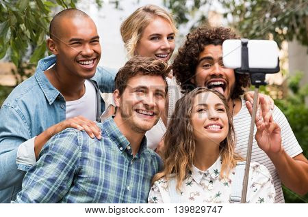 Happy friends with funny face taking a photo with a selfie stick. Group of smiling guys and girls taking picture by smartphone. Happy and cheerful young men and beautiful girls taking a selfie.