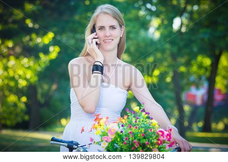 Portrait of pretty young female on bicycle with basket full of colorful flowers using smart phone. Summer, recreation and technology concepts.