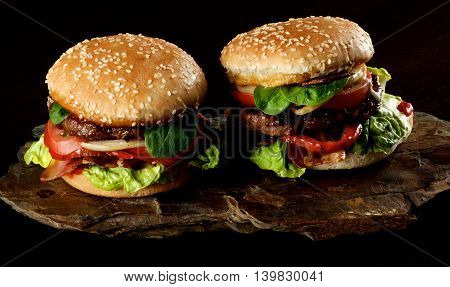 Two Tasty Hamburgers with Beef Bacon Lettuce Tomatoes Basil Roasted Onion and Juicy Sauce on Sesame Buns on Stone Board closeup on Dark background