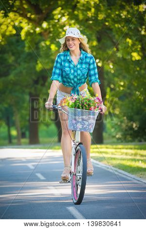 Pretty woman riding bicycle with basket full of flowers in a park. Active people, vacation, and lifestyle concepts.
