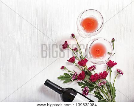 Bottle of wine, glasses and flowers on a wooden background