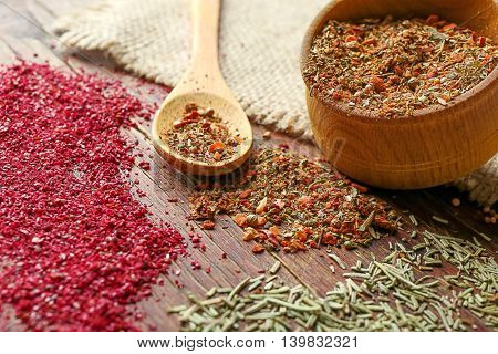 Mixed spices in bowl and spoon on wooden background