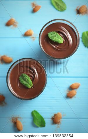 Chocolate mousse with mint in portion glasses on wooden background
