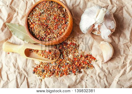 Mixed spices in wooden scoop and bowl on parchment background