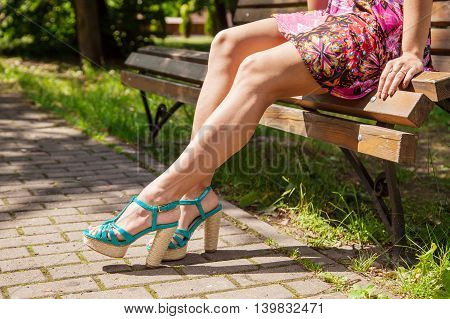 young girl in green shoes sitting on a park bench on summer. legs closeup