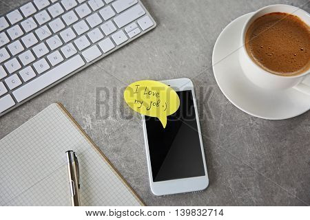 I love my job concept. Phone with yellow sticker on table