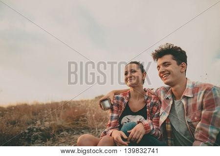 Young modern stylish couple in love smiling and hugging on autumn day outdoors. Hipsters having a cup of tea at nature.