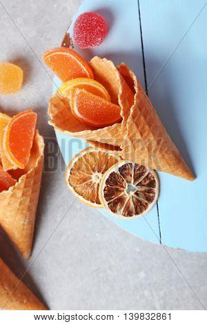 Dessert in ice cream cone on light background