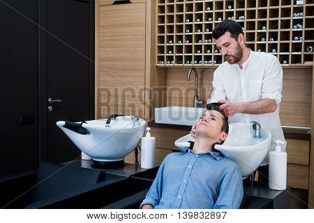 Hairstylist Hairdresser Washing Customer Hair - Young Man Relaxing In Hairdressing Beauty Salon.