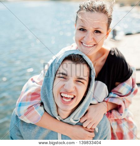 Happy teenage couple hugging and laughing by lake on a pier. Cheerful hipsters having fun outdoors on a sunny day