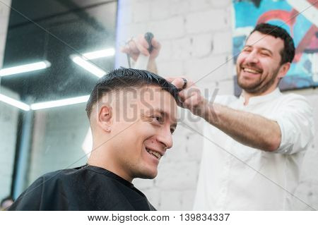 Male Barber Giving Client Haircut In Shop.