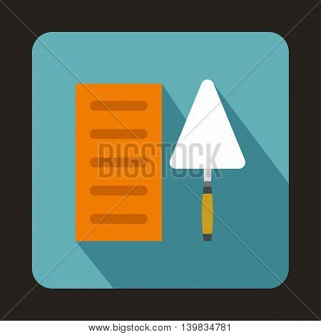 Building brick and construction trowel icon in flat style on a baby blue background