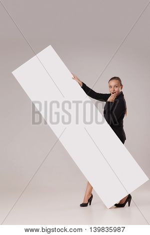 Happy woman with playful face expression behind blank copy space banner held diagonally isolated on white.