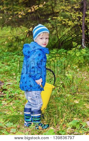 The boy gathers mushrooms in the forest. He stands in a forest clearing with a big bucket for mushrooms and looks into the camera
