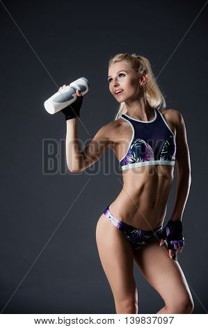 Slender sporty girl drinking water, resting after fitness exercises, tired, copy space.