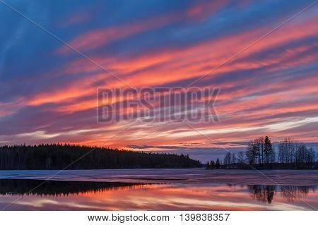 Early spring landscape with fire in clouds.