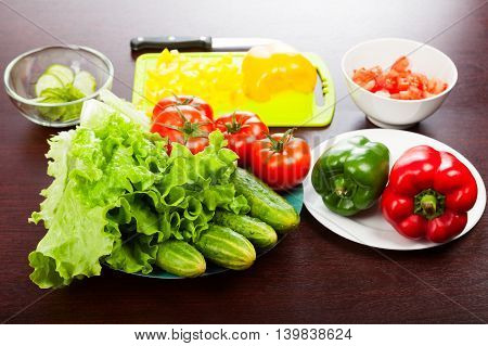 Lettuce with cucumbers tomatoes peppers cutting board and knife on the table. Pieces of chopped vegetables in the bowls.