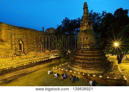 Candle light triple circumambulation activity around Buddha pagoda temple in Wat Maheyong Ayutthaya Thailand