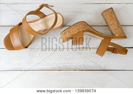 A new pair of stylish brown high heels with cork soles, beautiful shoes for ladies on white wooden background