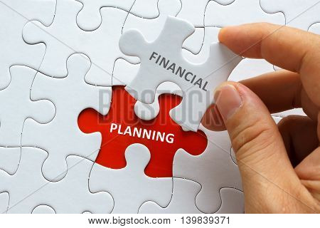 Hand Holding Piece Of Jigsaw Puzzle With Word Financial Planning.