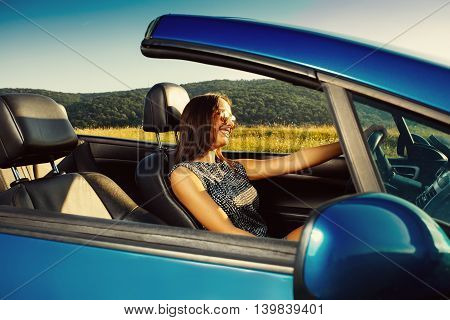Attractive young woman in a convertible traveling