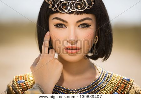 Portrait of young woman with luxury makeup. Beautiful girl with stylish haircut agaist desert background, young lady wearing fashionable golden necklace and dress. Beauty salon consept