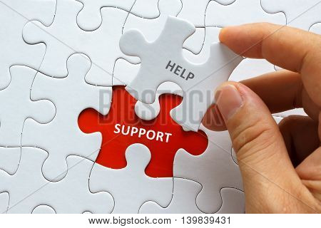 Hand Holding Piece Of Jigsaw Puzzle With Word Help Support.